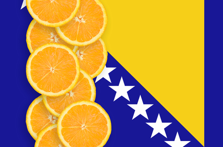 Bosnia and Herzegovina flag and vertical row of orange citrus fruit slices. Concept of growing as well as import and export of citrus fruits