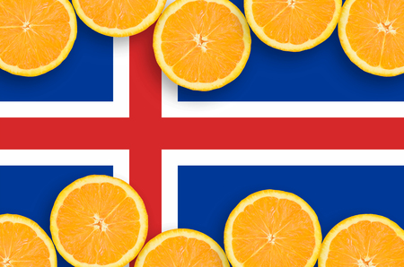 Iceland flag  in horizontal frame of orange citrus fruit slices. Concept of growing as well as import and export of citrus fruits Banco de Imagens
