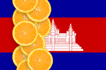 Cambodia flag and vertical row of orange citrus fruit slices. Concept of growing as well as import and export of citrus fruits Reklamní fotografie