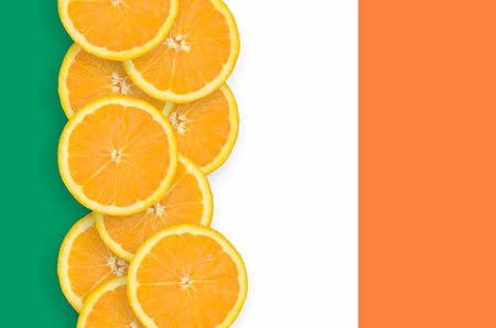 Ireland flag and vertical row of orange citrus fruit slices. Concept of growing as well as import and export of citrus fruits Banque d'images