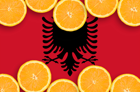 Albania flag  in horizontal frame of orange citrus fruit slices. Concept of growing as well as import and export of citrus fruits