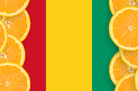 Guinea flag  in vertical frame of orange citrus fruit slices. Concept of growing as well as import and export of citrus fruits