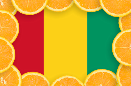 Guinea flag  in frame of orange citrus fruit slices. Concept of growing as well as import and export of citrus fruits Stock fotó