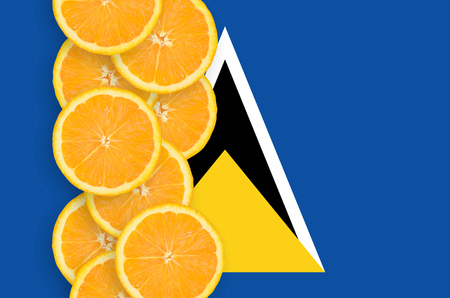 Saint Lucia flag and vertical row of orange citrus fruit slices. Concept of growing as well as import and export of citrus fruits