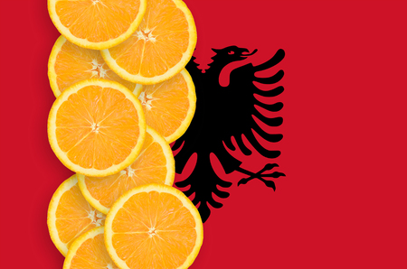 Albania flag and vertical row of orange citrus fruit slices. Concept of growing as well as import and export of citrus fruits