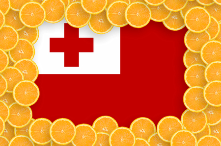 Tonga flag  in frame of orange citrus fruit slices. Concept of growing as well as import and export of citrus fruits Stock Photo