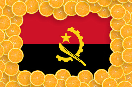 Angola flag  in frame of orange citrus fruit slices. Concept of growing as well as import and export of citrus fruits