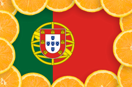Portugal flag  in frame of orange citrus fruit slices. Concept of growing as well as import and export of citrus fruits