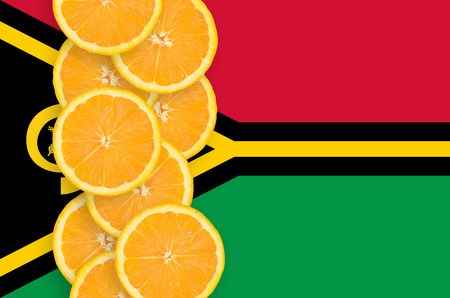 Vanuatu flag and vertical row of orange citrus fruit slices. Concept of growing as well as import and export of citrus fruits Banco de Imagens