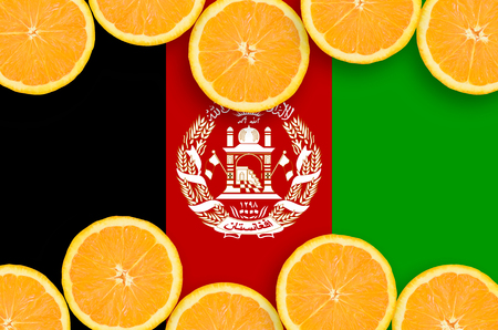 Afghanistan flag in horizontal frame of orange citrus fruit slices. Concept of growing as well as import and export of citrus fruits
