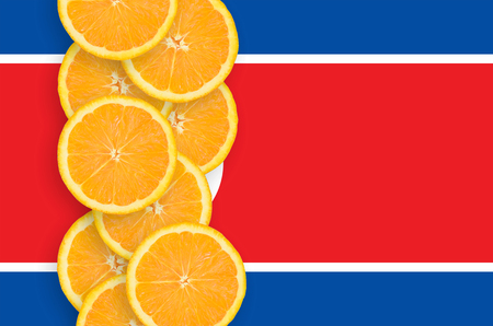 North Korea flag and vertical row of orange citrus fruit slices. Concept of growing as well as import and export of citrus fruits Foto de archivo