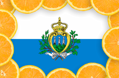 San Marino flag  in frame of orange citrus fruit slices. Concept of growing as well as import and export of citrus fruits