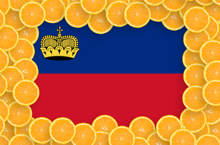 Liechtenstein flag  in frame of orange citrus fruit slices. Concept of growing as well as import and export of citrus fruits Stock Photo