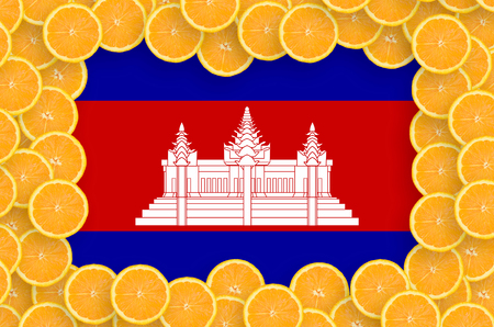 Cambodia flag  in frame of orange citrus fruit slices. Concept of growing as well as import and export of citrus fruits