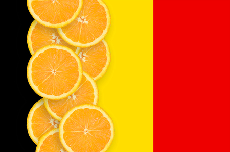 Belgium flag and vertical row of orange citrus fruit slices. Concept of growing as well as import and export of citrus fruits