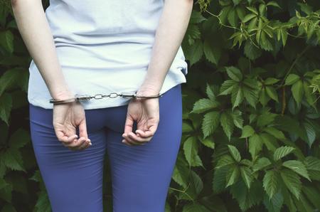 Fragment du corps d'une jeune fille criminelle avec les mains menottées sur fond de feuilles de lierre en fleurs vertes. Le concept de détention d'un délinquant d'une femme criminelle dans un environnement rural