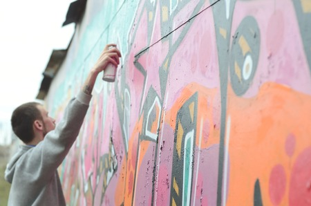 A young guy in a gray hoodie paints graffiti in pink and green colors on a wall in rainy weather. Focus on the fragment of wall and blurred artist