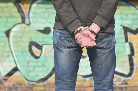 Back view of the arrested bandit from the ghetto against the background of the painted walls. The criminal was detained and his hands were handcuffed. The concept of combating crime Stock Photo