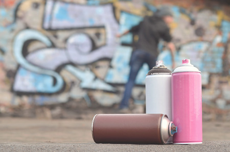 A photography of a certain number of paint cans against the background of the space with the wall on which the young guy draws a large graffiti drawing. Modern art of drawing walls in graffiti