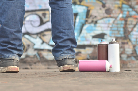 A still-life of several aerosol paint spray cans lies on a roofing covering on the background of a brick wall, on which is painted a bright and colorful graffiti drawing. Items related to street art Stock Photo