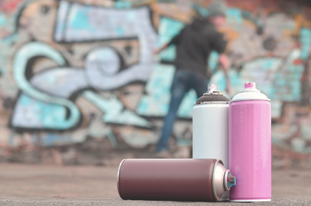 A still-life of several used paint cans of different colors against the wall, on which a young guy is applying graffiti-drawing. Concept street art and culture of youth art to paint the walls Stock Photo