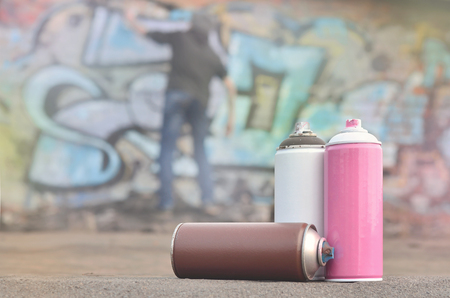 A conceptual image that shows the process of vandalism. The young man spoils the citys property, illegally drawing various drawings on the walls. Hooliganism called bombing or graffiti