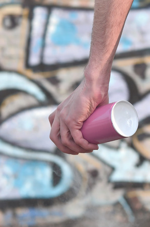 Photo of the hand of a street artist who draws a new color picture on a brick wall. One of the types of street art is the culture of youth graffiti. Decoration of walls of abandoned buildings Stock Photo