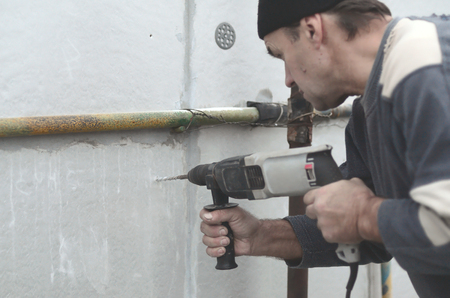 An elderly workman drills a hole in a  wall for the subsequent installation of a plastic reinforcing dowel. Creating holes in the wall with a drill. Warming of the building facade