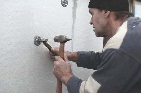 An elderly workman clogs a dowel into a plastic umbrella mount in a foam wall. The process of fixing expanded polystyrene plates. Warming of the facade of the building Stock Photo