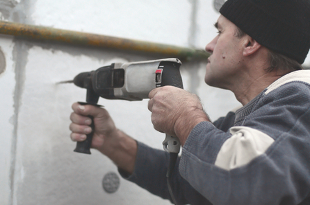 An elderly workman drills a hole in foam wall for the subsequent installation of a plastic reinforcing dowel. Creating holes in the wall with a drill. Warming of the building facade Stock Photo