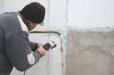 An elderly workman drills a hole in a foam wall for the subsequent installation of a plastic reinforcing dowel. Creating holes in the wall with a drill. Warming of the building facade