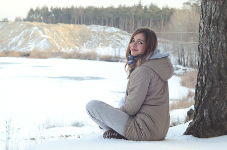 A young Caucasian girl in a brown coat is sitting near a cliff in the background of a horizon line between the sky and a frozen lake in winter time