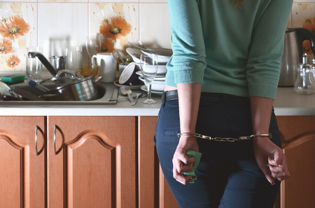 A girl with a sponge in her hand, handcuffed and tired of daily hand-washing dishes, stands next to the kitchen counter and a sink filled with a bunch of unwashed dishes. Female kitchen slavery Archivio Fotografico