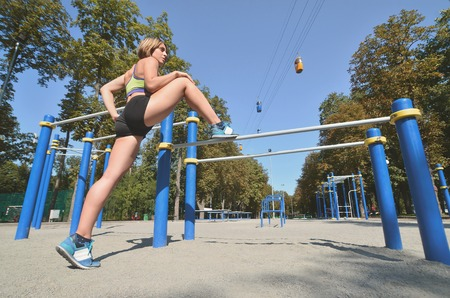 A young Caucasian female athlete in bright green sports clothes trains a stretch of legs on a sports gym for active outdoor recreation. Summer sports and healthy lifestyle