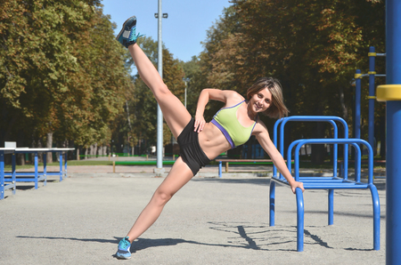 A young caucasian female athlete in bright green sport clothes practicing leg rides on the sports gym for active outdoor recreation. Summer sports and healthy lifestyle