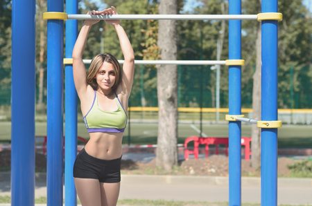 Young caucasian female in a bright green sportswear leaned against the horizontal bar on the sports field or playground. Photo of an athlete girl with a beautiful sports body