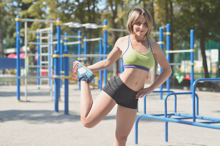 A young caucasian athlete girl in a bright green sportswear doing warm-up before training on playground for outdoor workout. Summer sports and healthy lifestyle concept Stock Photo