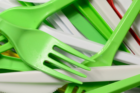 Pile of bright yellow, green and white used plastic kitchenware appliances. Ecological problem. Plastic pollution