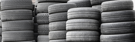 Old used tires stacked with high piles in secondary car parts shop garage close up