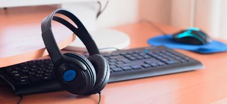 Big black headphones lie on the wooden desktop of the sound designer. Workplace for music creator. Selective focus