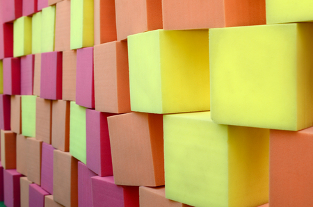Wall of yellow and red paralon soft cubes in dry pool, trampoline in the childrens gaming center