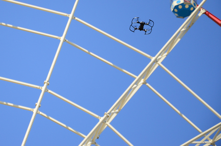 Drone with photocamera take off from land and flying for take photo front of ferris wheel