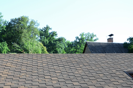 Modern roofing and decoration of chimneys. Flexible bitumen or slate shingles in rectangular shape in perspective.