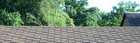 Modern roofing and decoration of chimneys. Flexible bitumen or slate shingles in rectangular shape in perspective. Stock Photo