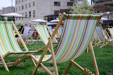 Chaise lounges on a lawn. Rest in the festival, on vacation. Garden sunbeds on green grass. Garden bed for sunbathing and rest. Summer chair 写真素材
