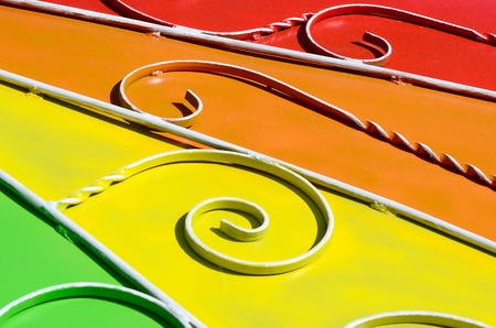 Metal texture of a piece of colored wall with a forged pattern. Rainbow colors 版權商用圖片