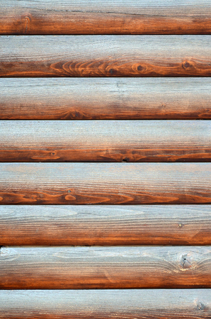 Hewn timber. Rustic log wall horizontal timber background. Fragment of unpainted wooden debarked logs. House wall wallpaper texture