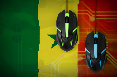 Senegal flag  and two modern computer mice with backlight. The concept of online cooperative games. Cyber sport team Stock Photo