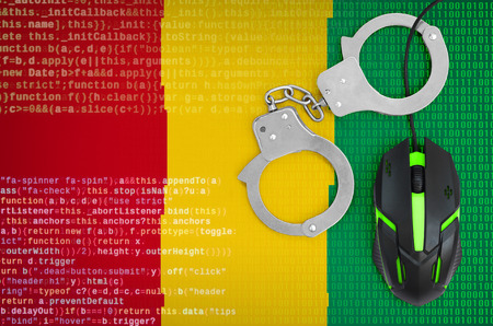 Guinea flag  and handcuffed modern backlit computer mouse. Creative concept of combating computer crime, hackers and piracy