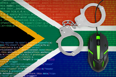 South Africa flag  and handcuffed modern backlit computer mouse. Creative concept of combating computer crime, hackers and piracy